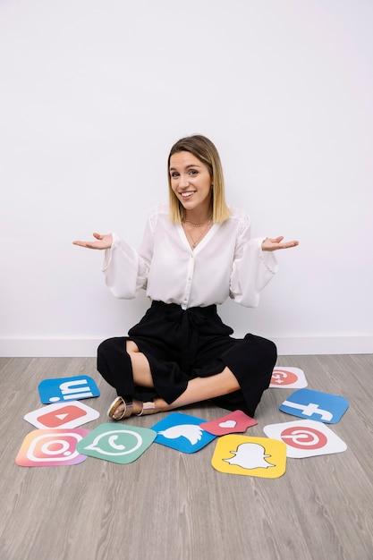 Portret bizneswomanu obsiadanie z ogólnospołeczny medialny ikon gestykulować Darmowe Zdjęcia