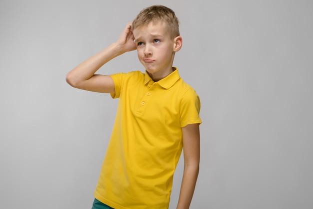 Portret blondynki caucasian smutny chłopiec w żółtym tshirt słuchaniu na szarości ścianie Premium Zdjęcia