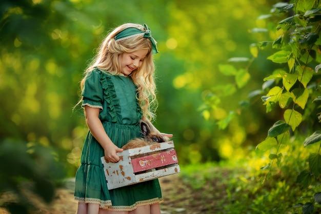 Portret Blondynki Dziewczyny W Zielonej Rustykalnej Sukni W Lecie Na Spacerze, Który Trzyma Królika W Małym Drewnianym Pudełku W Rękach. Premium Zdjęcia