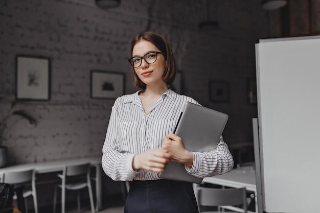 Portret Brązowooka Biznesowa Kobieta W Czarno-białym Stroju I Stylowe Okulary Z Laptopem W Białym Pokoju. Darmowe Zdjęcia