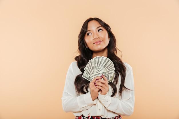 Portret Brunetki Azjatykci żeński żeński Przyglądający Up Podczas Gdy Trzymający Fan 100 Dolarowych Rachunków Jest Pomyślnym Bizneswomanem Nad Brzoskwini Tłem Darmowe Zdjęcia