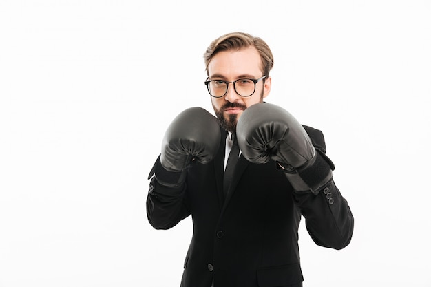 Portret Brunetki Mężczyzna W Czarnym Kostiumu, Eyeglasses I Pozować W Bokserskich Rękawiczkach, Odizolowywający Nad Biel ścianą Premium Zdjęcia