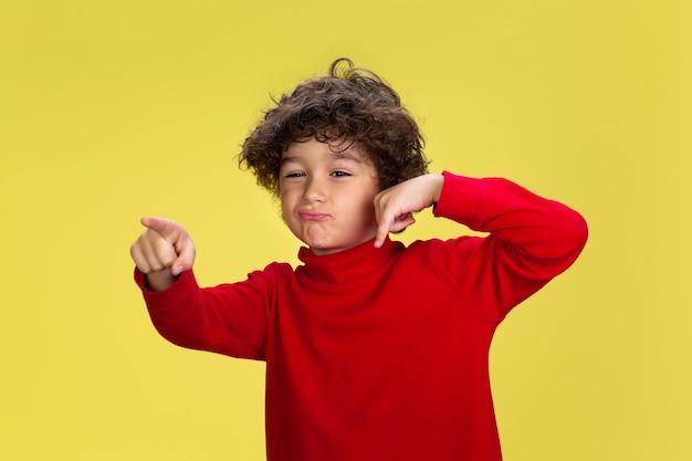 Portret Całkiem Młody Chłopak Kręcone W Czerwonym Nosić Na żółtym Tle Studio. Dzieciństwo, Ekspresja, Edukacja, Koncepcja Zabawy. Darmowe Zdjęcia