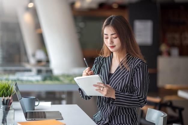 Portret Całkiem Młodych Bizneswoman Azjatyckiego, Biorąc Uwagę I Przy Użyciu Komputera Przenośnego W Nowoczesnym Biurze Premium Zdjęcia
