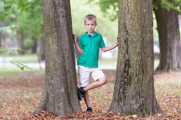 Portret Całkiem Słodkie Dziecko Chłopiec Stojący W Pobliżu Duży Pień Drzewa W Lecie Parku Na Zewnątrz. Premium Zdjęcia