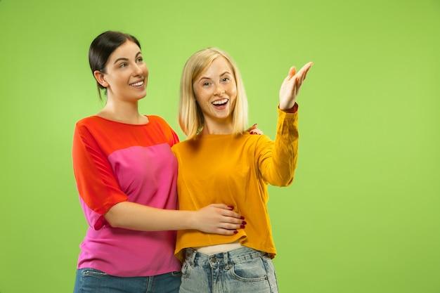 Portret Całkiem Urocze Dziewczyny W Casualowych Strojach Na Białym Tle Na Zielonej Przestrzeni. Dwie Modelki Jako Dziewczyny Lub Lesbijki Darmowe Zdjęcia