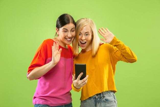 Portret Całkiem Urocze Dziewczyny W Casualowych Strojach Na Białym Tle Na Zielonej Przestrzeni. Dziewczyny Lub Lesbijki Robią Selfie Darmowe Zdjęcia