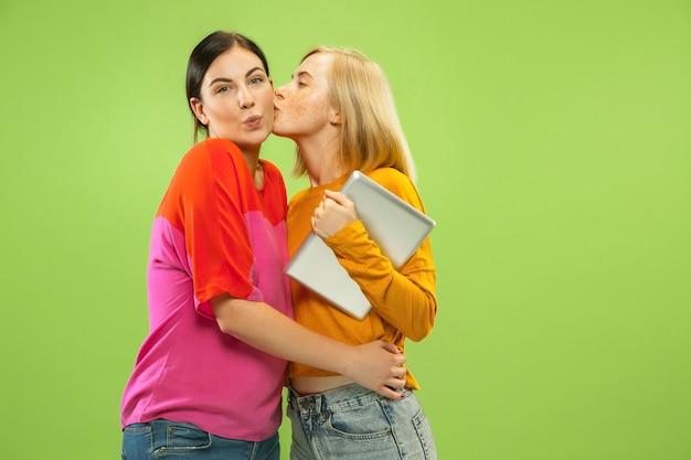 Portret Całkiem Urocze Dziewczyny W Casualowych Strojach Na Białym Tle Na Zielonej Przestrzeni. Dziewczyny Lub Lesbijki Używające Tabletu Do Zabawy Lub Płatności Darmowe Zdjęcia