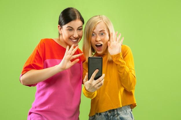 Portret Całkiem Urocze Dziewczyny W Zwykłych Strojach Na Białym Tle Na Zielonej ścianie. Dziewczyny Lub Lesbijki Robią Selfie. Pojęcie Lgbt, Równość, Ludzkie Emocje, Miłość, Relacja. Darmowe Zdjęcia