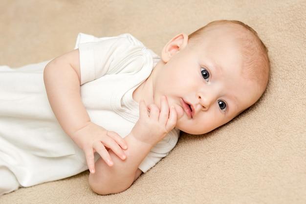 Portret Cute Baby Boy W Białych Strojach Leżącego Na Beżowym łóżku Premium Zdjęcia