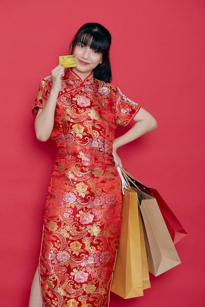 Portret Cute Młoda Kobieta Azji Nosić Chińską Sukienkę Z Torbą Na Zakupy I Kartą Kredytową Na Chiński Nowy Rok Na Czerwonej ścianie Premium Zdjęcia