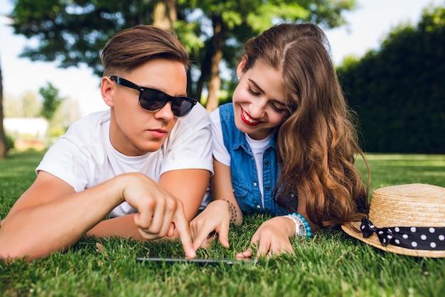 Portret Cute Para, Leżąc Na Trawie W Parku Latem. Dziewczyna Z Długimi Kręconymi Włosami, Czerwone Usta Uśmiecha Się Do Tabletki Na Trawie. Przystojny Facet W Białej Koszulce Pokazuje Na Ekranie. Darmowe Zdjęcia