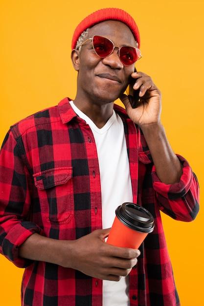 Portret Czarnego Amerykanina Przystojnego Stylowego Mężczyzna Jest Ubranym W Kratkę Czerwonawą Koszula Trzyma Napój Filiżanka Kawową Przerwę Z Telefonu Kolorem żółtym Premium Zdjęcia
