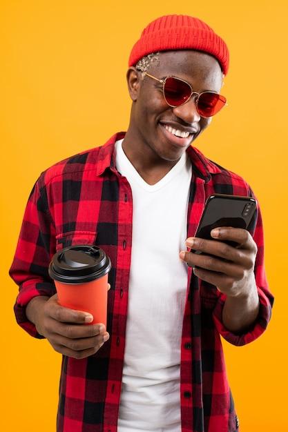 Portret Czarny Amerykański Mężczyzna Ubierał Stylowo Trzymać Szklankę Napoju Na Kawowej Przerwie Z Telefonu Kolorem żółtym Premium Zdjęcia
