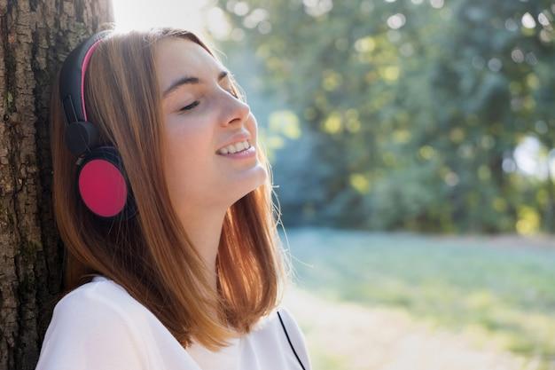 Portret Czerwona Z Włosami Nastoletnia Dziewczyna Słucha Muzyka W Dużych Różowych Słuchawkach Outdoors Opiera Opiera Drzewo. Premium Zdjęcia