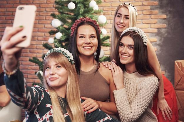 Portret Cztery Uśmiechniętej Dziewczyny Z Koroną Na Głowie Robi Selfie Fotografii. Nowy Rok Wesołych świąt Premium Zdjęcia