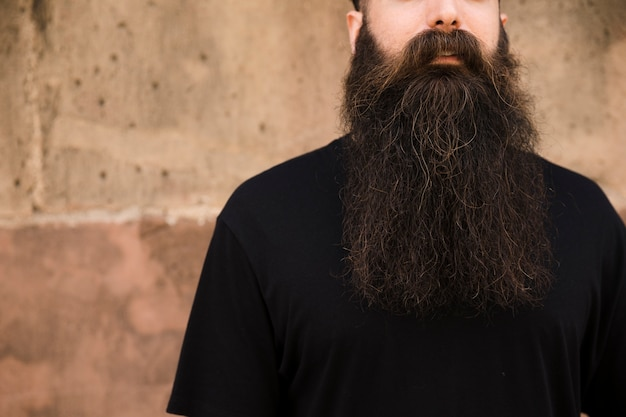 Portret długi brodaty młody człowiek przed ścianą Darmowe Zdjęcia