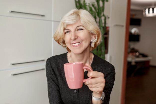 Portret Dobrze Wyglądający Dojrzała Zdrowa Szczupła Kobieta Z Filiżanką Kawy Pozuje W Jej Nowożytnej Kuchni Darmowe Zdjęcia