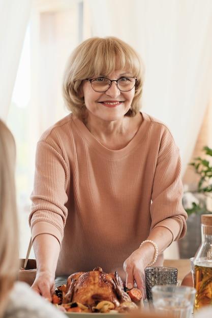 Portret Dojrzałej Blondynki W Okularach Serwowane Danie Z Indykiem Na Stole Na święto Dziękczynienia Premium Zdjęcia