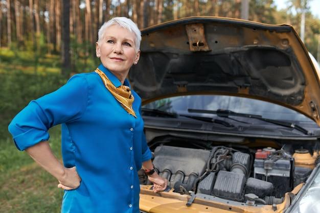 Portret Dojrzałej Kobiety Z Krótkimi Blond Włosami O Sfrustrowanym Wyrazie Twarzy, Ponieważ Samochód Jest Uszkodzony. Zestresowana Kobieta W średnim Wieku Czekająca Na Usługę Po Awarii Pojazdu, Otwierająca Maskę Darmowe Zdjęcia