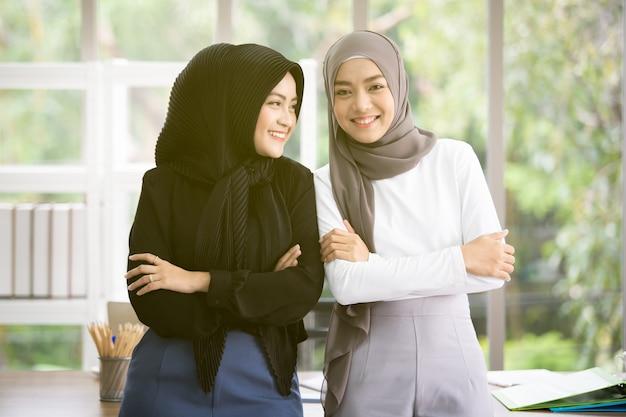 Portret Dwa Azjatyckiej Muzułmańskiej Kobiety Opowiada Wpólnie W Biurze Premium Zdjęcia