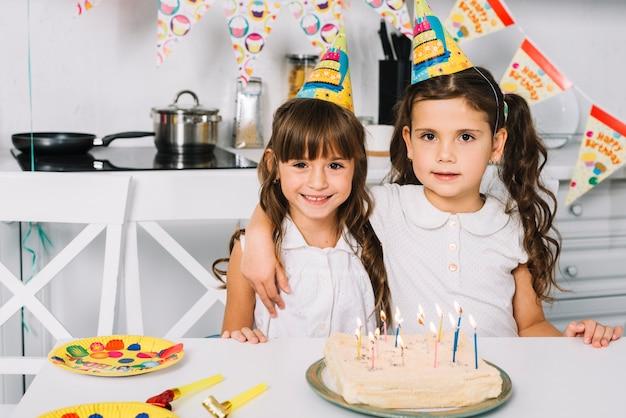 Portret dwa uśmiechniętej dziewczyny z partyjnymi kapeluszami na kierowniczej pozyci za urodzinowym tortem Darmowe Zdjęcia