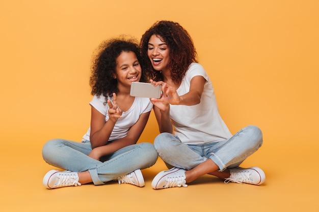 Portret Dwie Radosnej Afro Amerykańskiej Siostry Bierze Selfie Z Smartphone Darmowe Zdjęcia