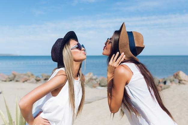 Portret Dwóch Atrakcyjnych Brunetek I Blond Dziewczyn Z Długimi Włosami Stoją Na Plaży W Pobliżu Morza. Pokazują Pocałunek. Darmowe Zdjęcia