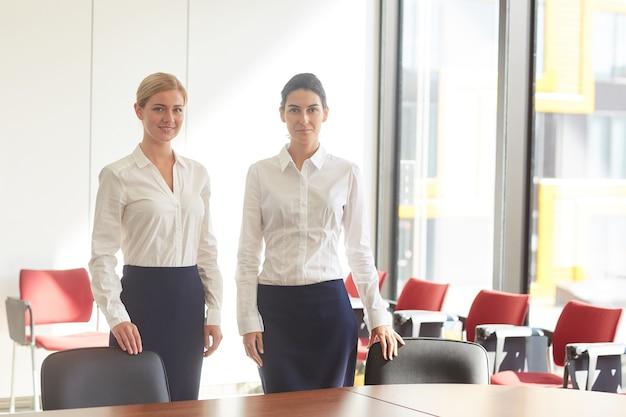 Portret Dwóch Eleganckich Kobiet Biznesu Ubranych W Czarno-białe Stojących W Pustej Sali Konferencyjnej Premium Zdjęcia