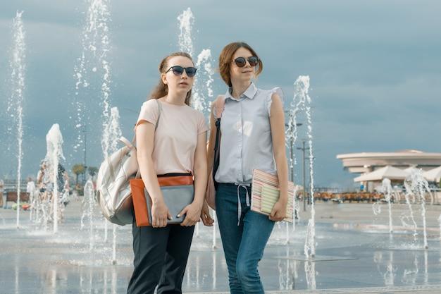 Portret dwóch młodych pięknych dziewczyn z plecakami w pobliżu fontanny Premium Zdjęcia