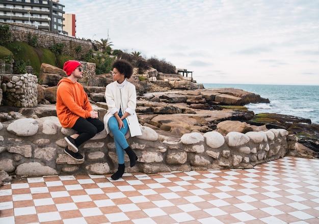 Portret Dwóch Młodych Przyjaciół Spędzających Miło Czas I Rozmawiających, Siedząc Z Morzem W Kosmosie. Darmowe Zdjęcia