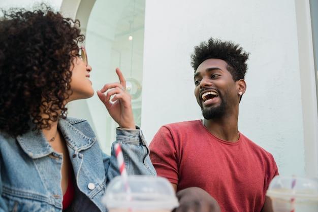 Portret Dwóch Przyjaciół Afro, Którzy Razem Bawią Się I Cieszą Się Dobrym Czasem, Pijąc świeży Sok Owocowy Na świeżym Powietrzu W Kawiarni. Premium Zdjęcia