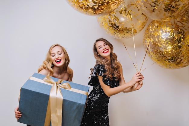 Portret Dwóch Radosnych Podekscytowanych Wspaniałych Kobiet Z Długimi Kręconymi Włosami świętującymi Urodziny Na Białej Przestrzeni. Duży Prezent, Balony Ze Złotymi świecidełkami, Darmowe Zdjęcia