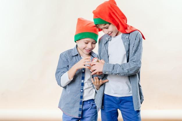 Portret Dwóch Szczęśliwych Braci W Czerwonych Czapkach świętego Mikołaja Premium Zdjęcia