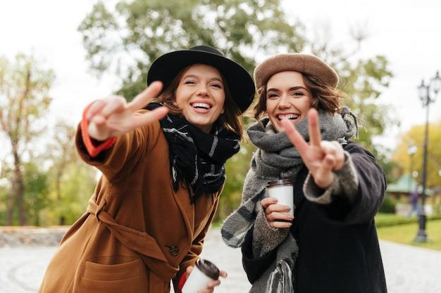Portret Dwóch Uśmiechniętych Dziewcząt Ubranych W Płaszcze Darmowe Zdjęcia