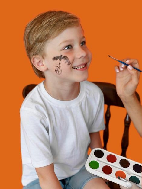 Portret Dziecka Buźkę Z Twarzą Namalowaną Na Halloween Darmowe Zdjęcia