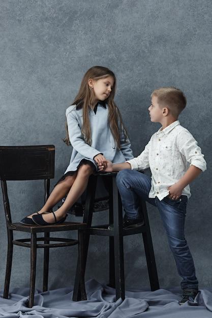 Portret Dziewczynki I Chłopca Na Szarej ścianie Darmowe Zdjęcia