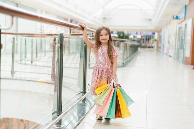 Portret Dziewczynki Szczęśliwy W Centrum Handlowym. Uśmiechnięta Dziewczyna W Różowej Sukience Z Wielobarwnymi Torbami W Dłoniach Jest Zaangażowana W Zakupy. Szablon Twojego Ogłoszenia. Premium Zdjęcia