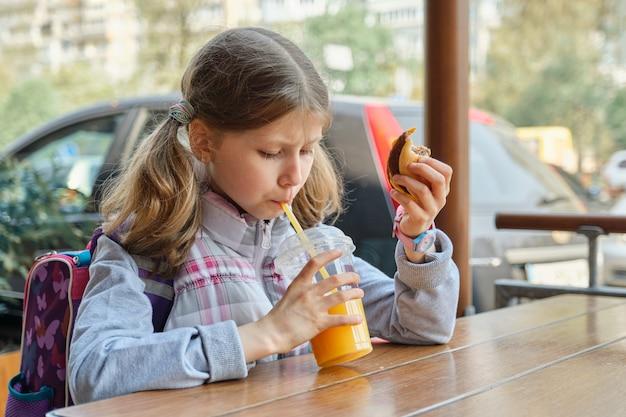 Portret Dziewczynki Z Plecakiem, Jedzenie Hamburgera I Picie Soku Pomarańczowego Premium Zdjęcia