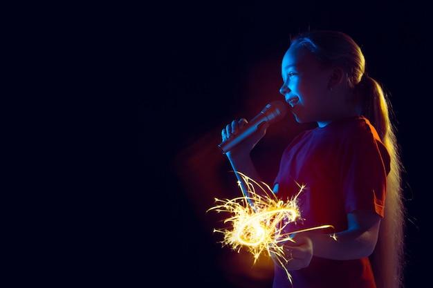 Portret Dziewczyny Kaukaski Na Ciemnym Tle Studio W świetle Neonu. Piękna Modelka Z Głośnikiem I Brylantem. Darmowe Zdjęcia