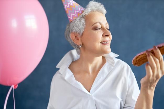 Portret Ekstatycznej Szczęśliwej Emerytki W Stylowej Białej Koszuli I Stożkowym Kapeluszu Tańczy Do Muzyki Na Przyjęciu Urodzinowym, Trzymając Różowy Balon Z Helem. Darmowe Zdjęcia