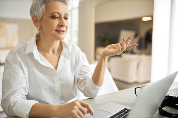 Portret Energicznej, Odnoszącej Sukcesy, Dojrzałej Bizneswoman W Białej Koszuli, Mającej Spotkanie Biznesowe Online Za Pośrednictwem Wideokonferencji, Gestykulując Emocjonalnie, Omawiając Umowę Darmowe Zdjęcia