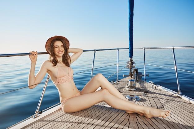 Portret Gorącej Atrakcyjnej Dorosłej Kobiety, Siedzącej Na Dziobie Jachtu, Mrugającej W Bikini I Słomkowym Kapeluszu. ładna Kobieta Opalająca Się, Aby Uzyskać Lepszą Opaleniznę Podczas Wakacji Za Granicą. Darmowe Zdjęcia