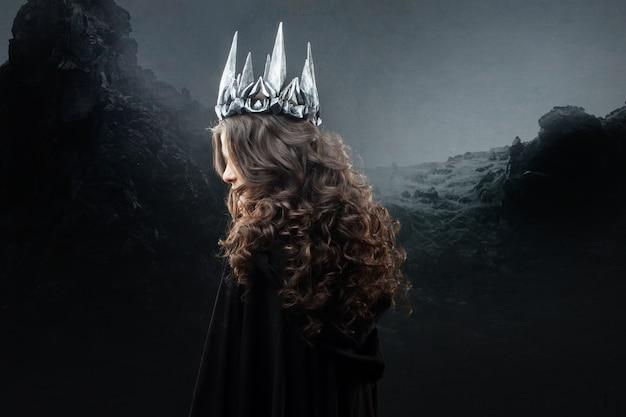 Portret Gotyckiej Księżniczki. Piękna Młoda Brunetki Kobieta W Metal Koronie I Czarnej Pelerynie. Premium Zdjęcia