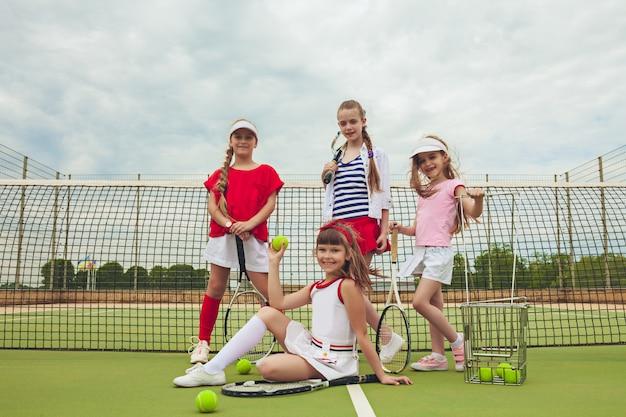Portret Grupa Dziewczyny Jako Gracz W Tenisa Trzyma Tenisowego Kant Przeciw Zielonej Trawie Plenerowy Sąd Darmowe Zdjęcia
