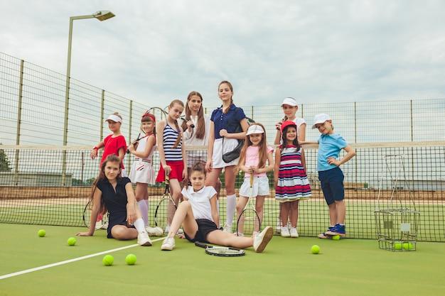 Portret Grupy Dziewcząt I Chłopców Jako Tenisistów Trzymających Rakiety Tenisowe Przed Zieloną Trawą Odkryty Kort. Darmowe Zdjęcia