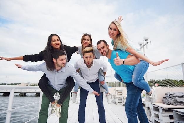 Portret Grupy Młodych Ludzi Siedzących Na Skraju Molo, Na Zewnątrz W Przyrodzie. Przyjaciele Bawią Się W Grę Na Jeziorze. Darmowe Zdjęcia
