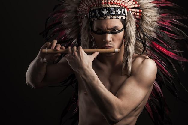 Portret Indyjski Silny Mężczyzna Pozuje Z Tradycyjnym Rodowitym Amerykaninem Uzupełniał. Gra Na Flecie Premium Zdjęcia