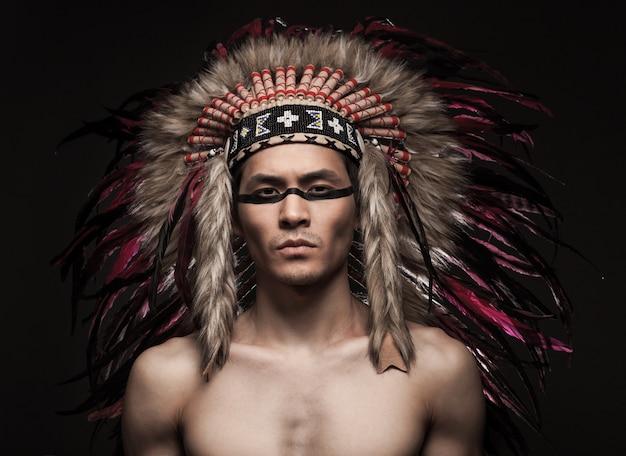 Portret Indyjski Silny Mężczyzna Pozuje Z Tradycyjnym Rodowitym Amerykaninem Uzupełniał Premium Zdjęcia