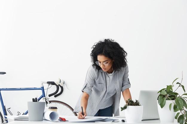 Portret Inżyniera Kobiety O Ciemnych Kręconych Włosach Na Sobie Zwykłą Koszulę Darmowe Zdjęcia